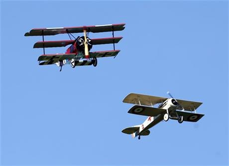 A World War 1-era Fokker DR-1 tri-plane and Spad VII bi-plane, both reproductions, perform a dog fight during an air show at the Old Rhinebeck Aerodrome on Sunday, July 6, 2014, in Rhinebeck, N.Y. (AP Photo/Mike Groll)